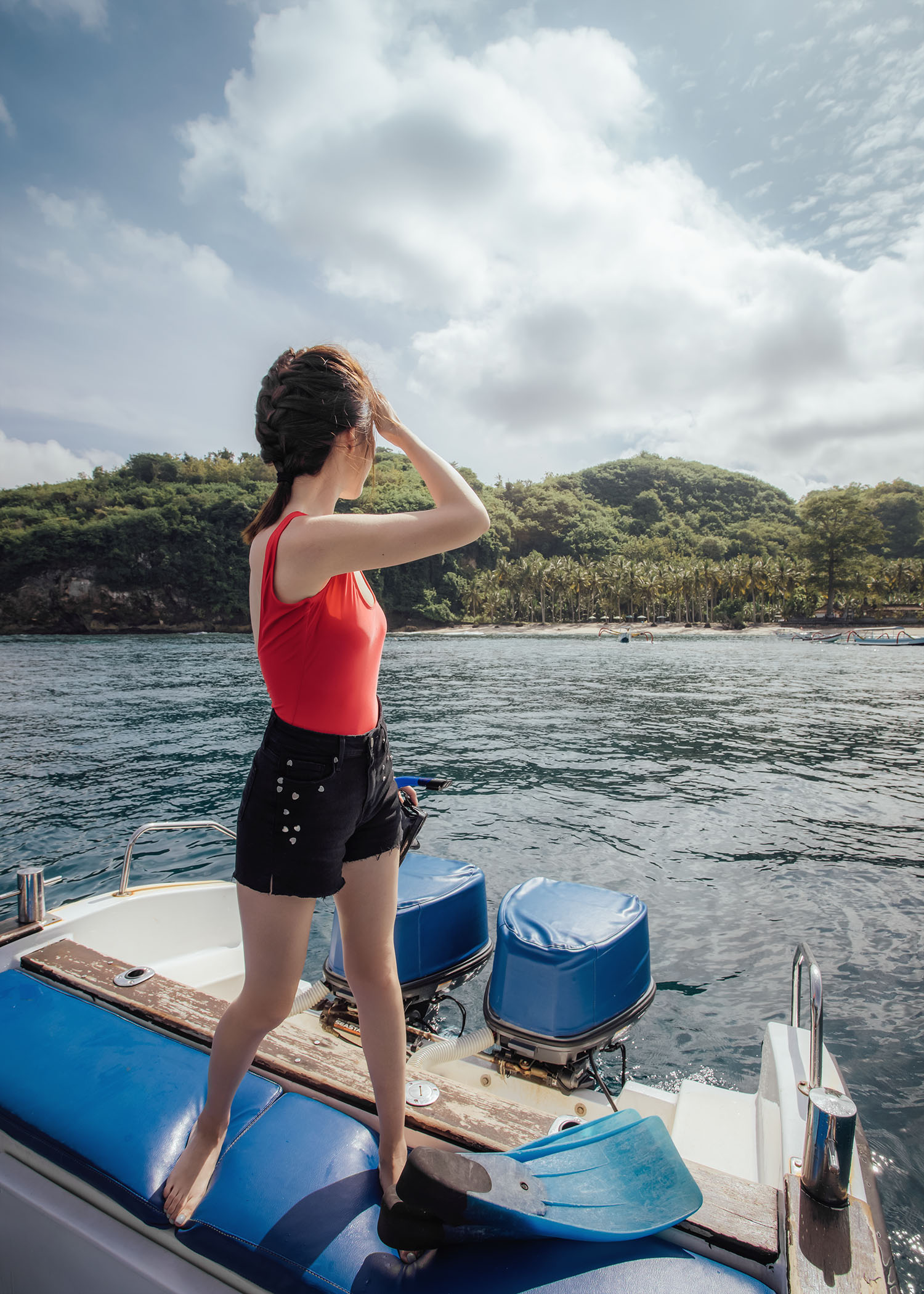 Fashion and travel blogger influencer Jenny Tsang of Tsangtastic traveling in Bali, Indonesia, wearing COVER Tank Swimsuit, PAIGE Heart Shorts, while snorkeling.