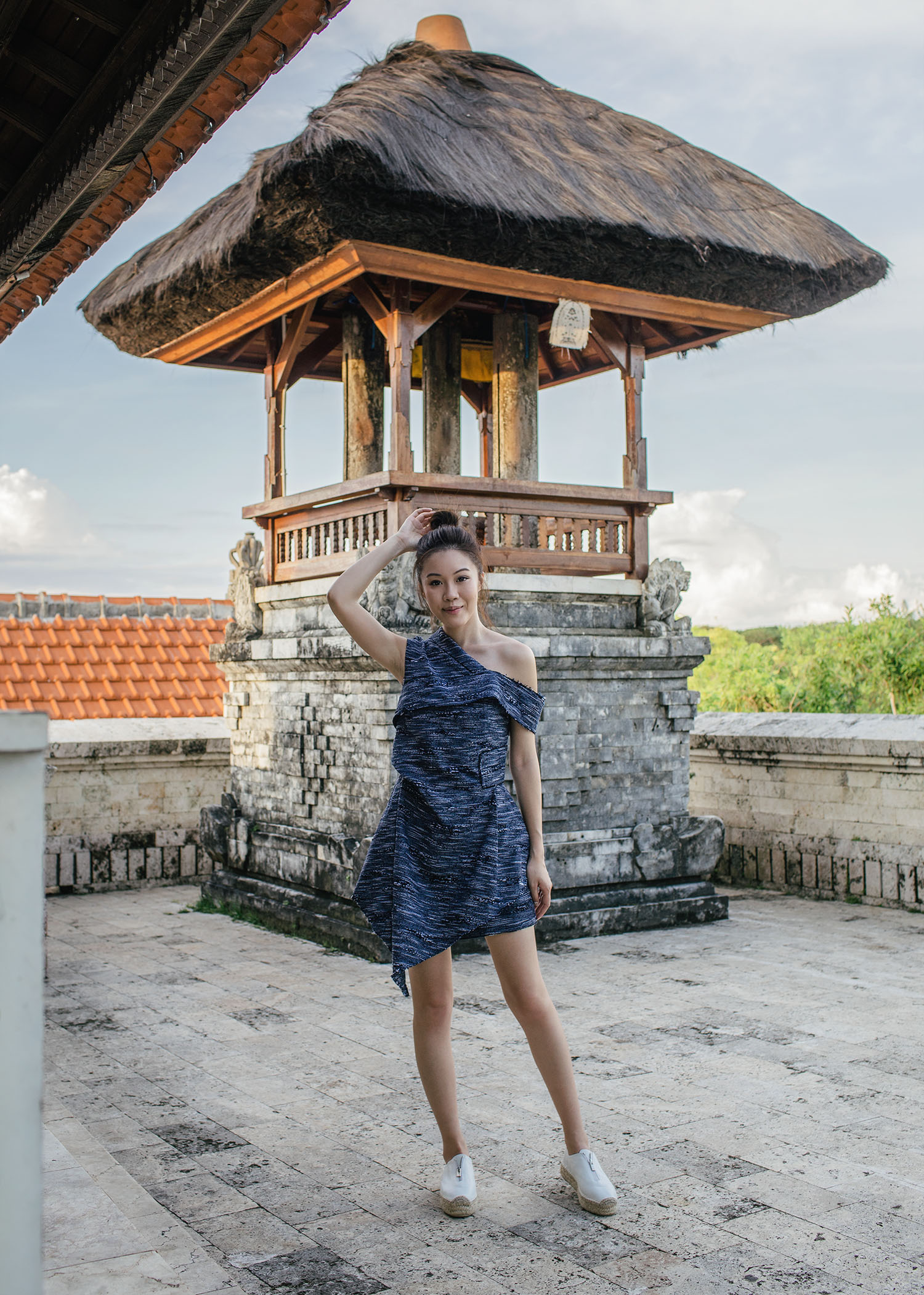 Fashion and travel blogger influencer Jenny Tsang of Tsangtastic traveling in Bali, Indonesia, wearing ACLER Top, at Uluwatu Temple.