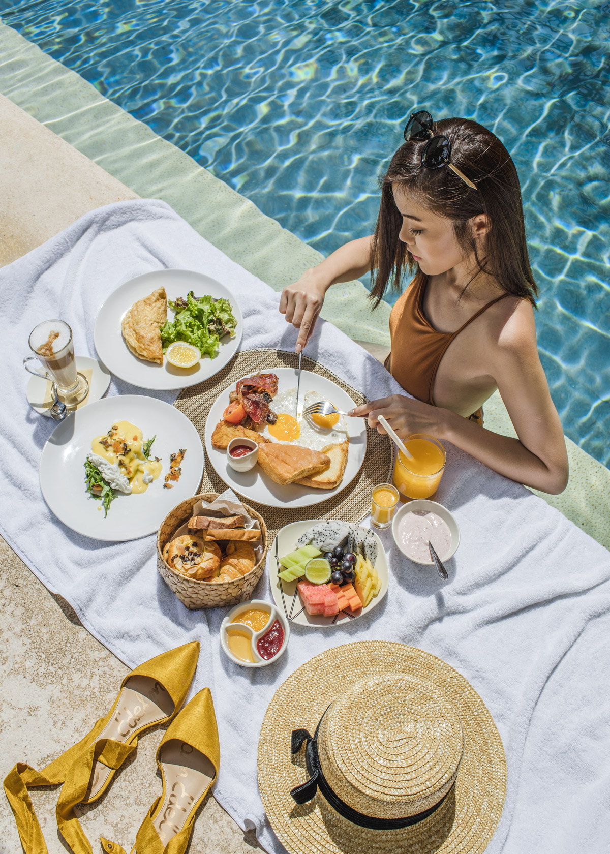 Fashion and travel blogger influencer Jenny Tsang of Tsangtastic traveling in Bali, Indonesia, wearing MIDSOMMAR Swim, enjoying breakfast at the pool.