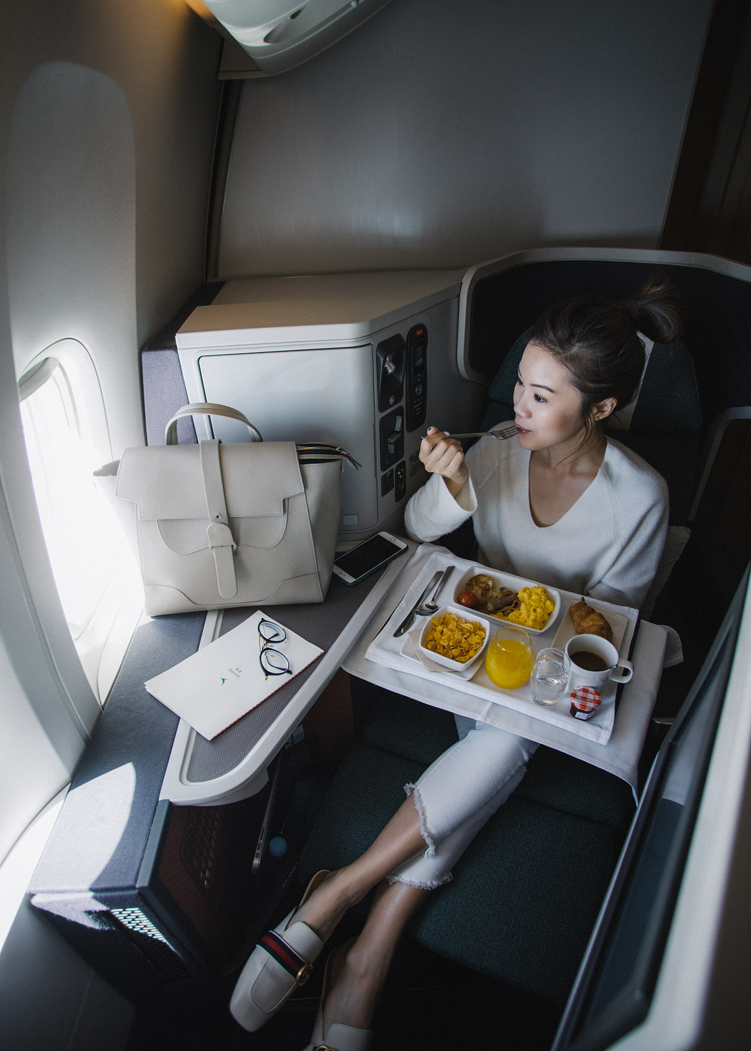 Fashion and travel blogger influencer Jenny Tsang of Tsangtastic traveling in Hong Kong, with Cathay Pacific in business class, wearing Vince Cashmere Off Shoulder Sweater and Gucci White Leather Slipper.