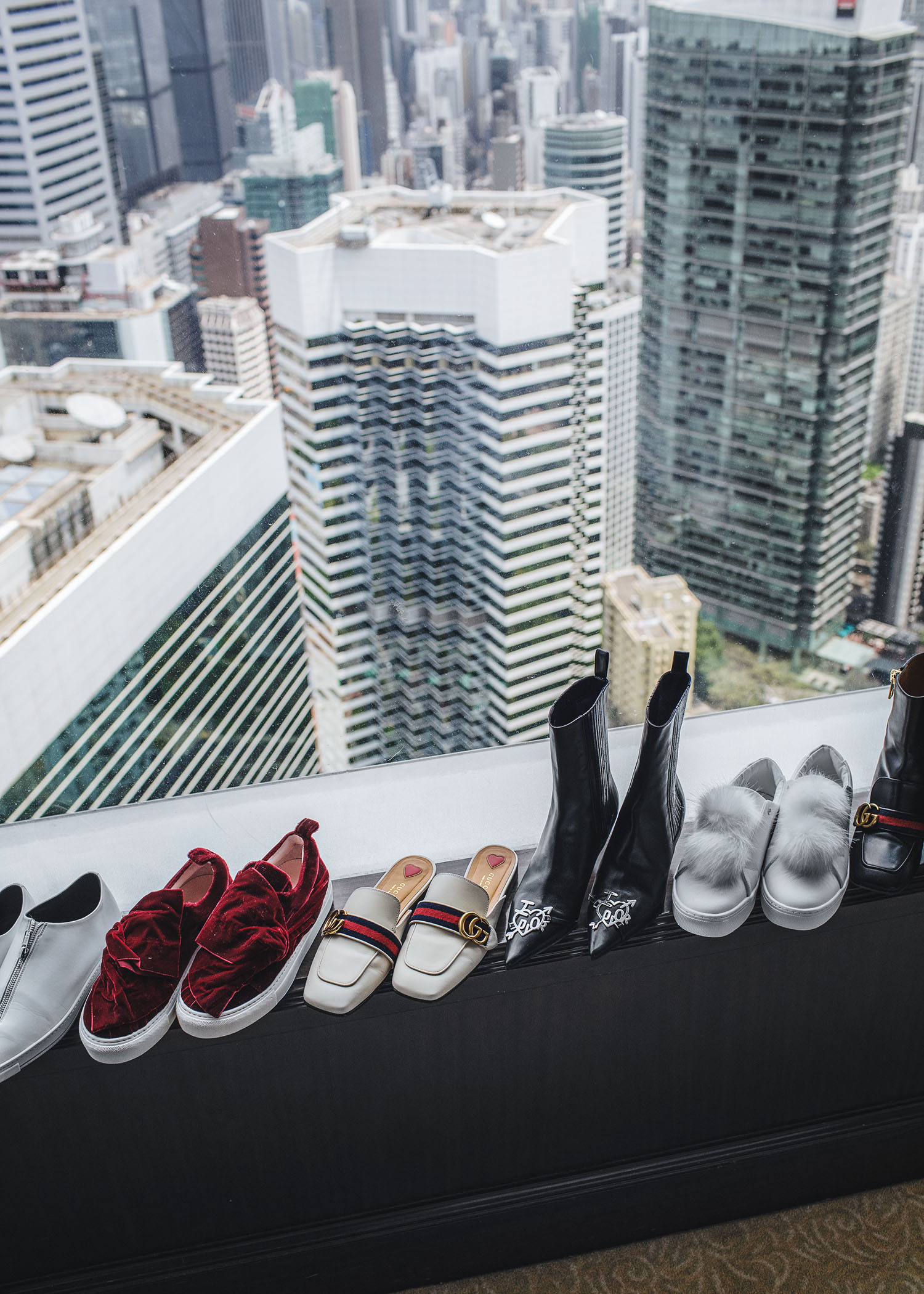 Fashion and travel blogger influencer Jenny Tsang of Tsangtastic traveling in Hong Kong, at the Island Shangri-La Hotel. Shoe collection, Stella McCartney Zip Sneaker, Josefinas Red Velvet Louise Bow Sneaker, Gucci White Leather Slipper, Dior 'I Love Dior' Pointed Boots, Gucci Pearl Boots.