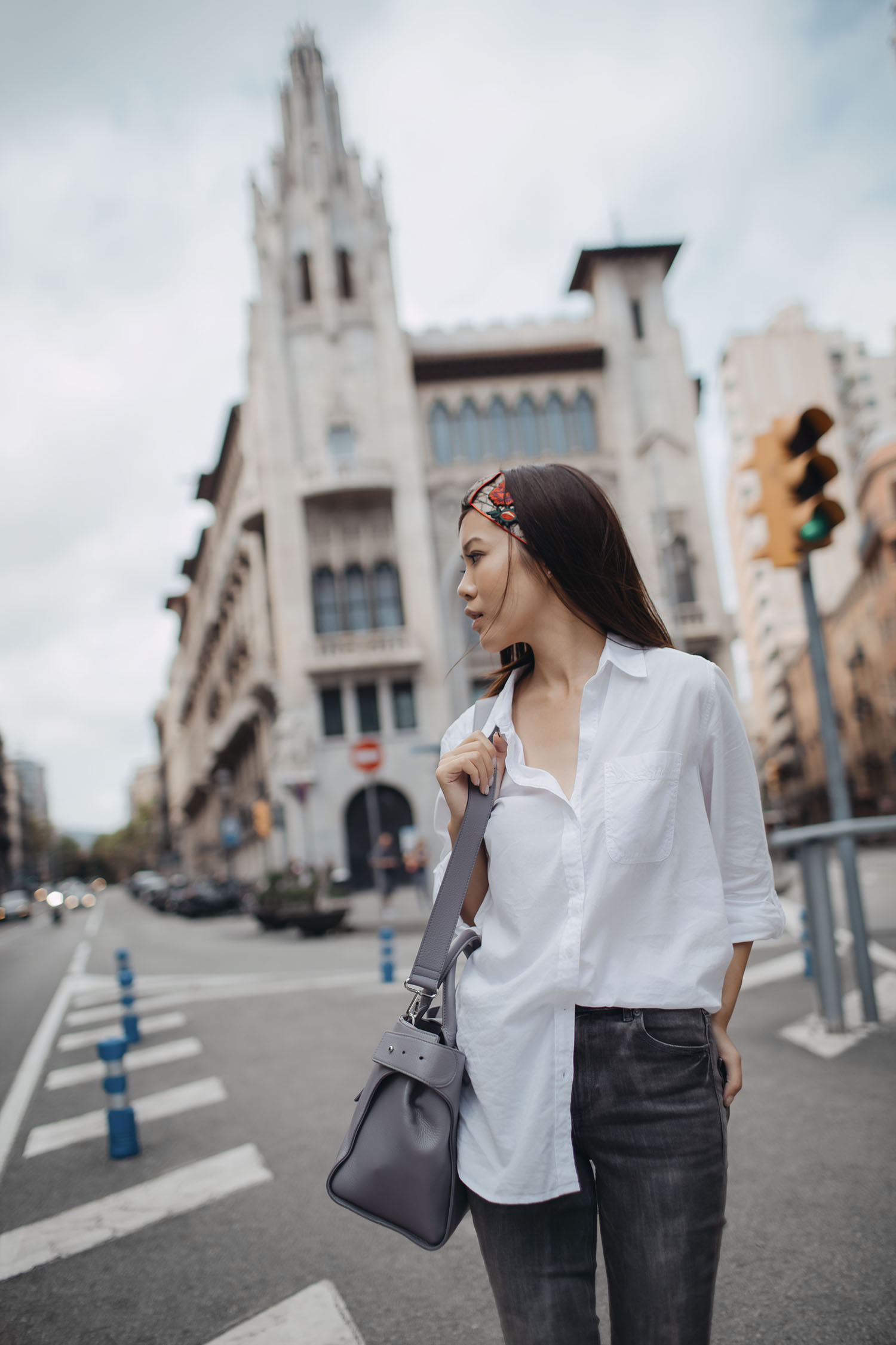 Lifestyle fashion travel blogger Jenny Tsang of Tsangtastic wearing off Gucci headband white button down shirt grey raw hem skinny jeans and roger vivier grey sneakers in Barcelona Spain