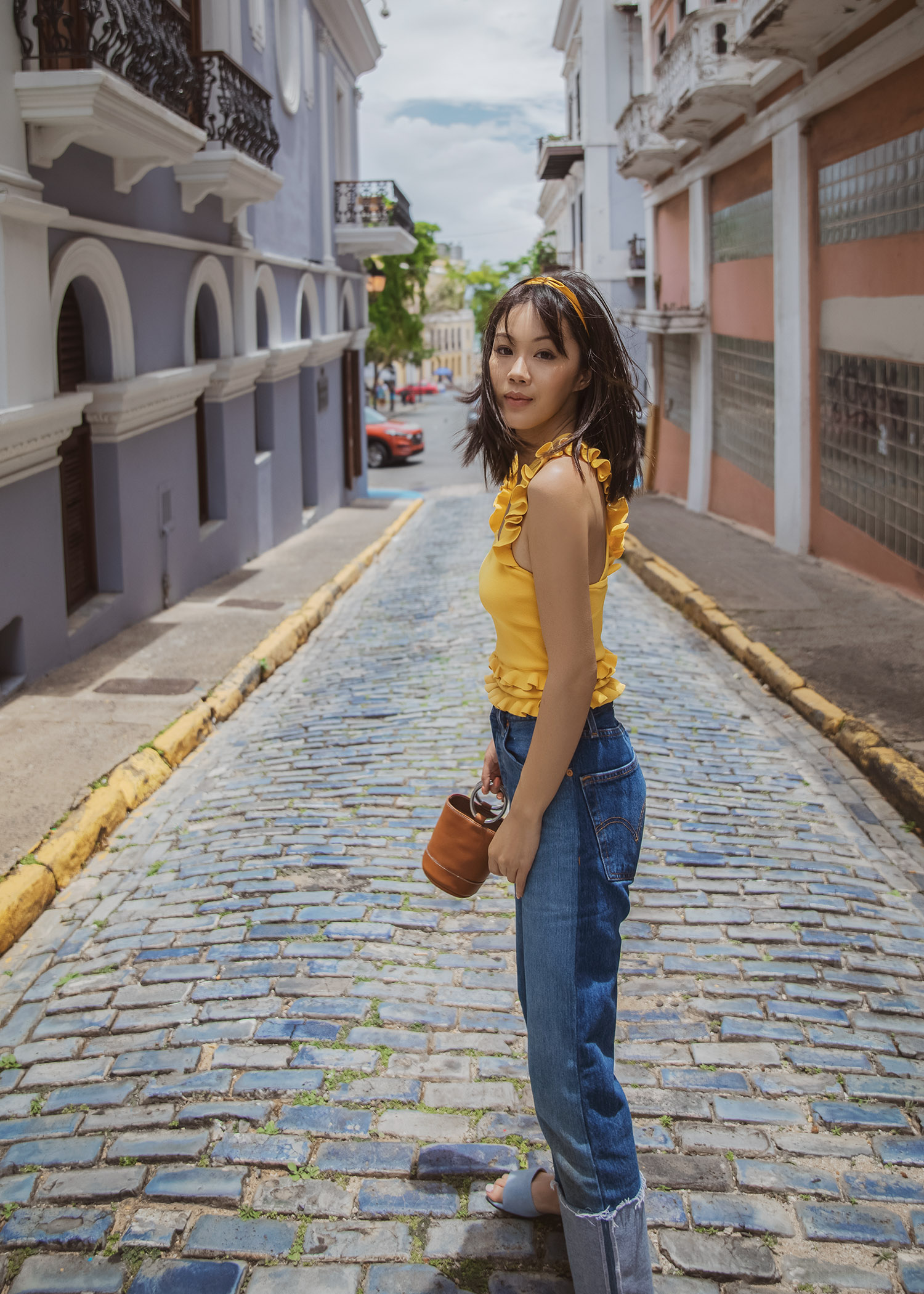 Jenny of Tsangtastic in Puerto Rico wearing yellow tank style ruffle trim top re/done cuffed jeans
