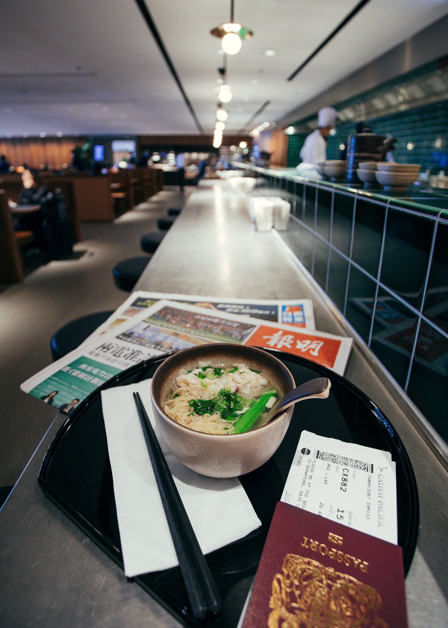 Fashion and travel blogger influencer Jenny Tsang of Tsangtastic traveling in Hong Kong, with Cathay Pacific, in business lounge enjoying the noodle bar.
