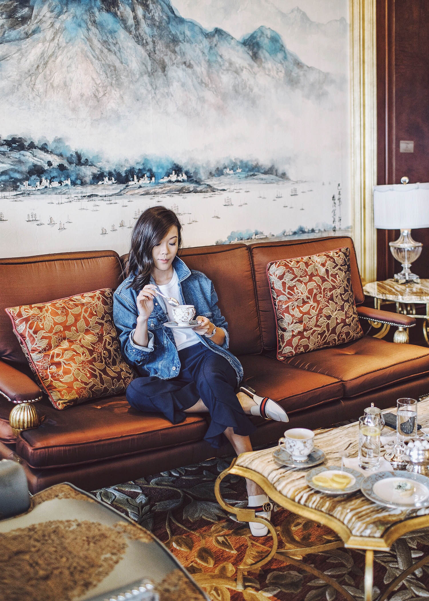 Fashion and travel blogger influencer Jenny Tsang of Tsangtastic traveling in Hong Kong, wearing H&M Denim Lace-Up Jacket, C/MEO COLLECTIVE Pants, GUCCI White Leather Slipper, at the Island Shangri-La Hotel.