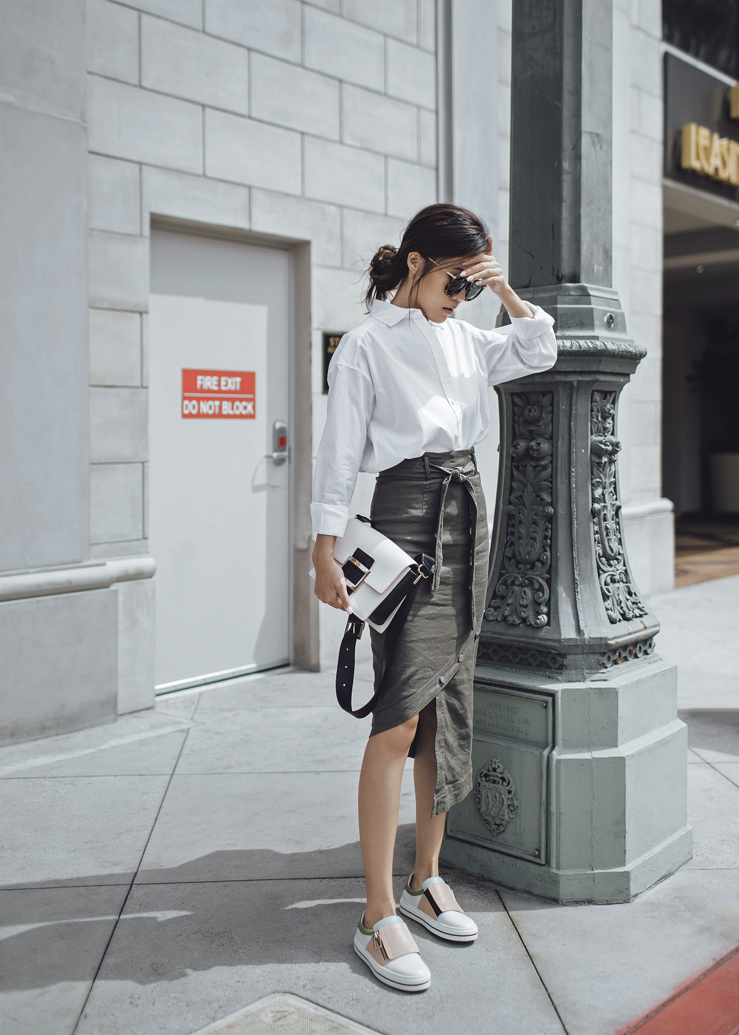 Midi skirt outfit Street style fashion blogger influencer Jenny Tsang of Tsangtastic wearing white button down shirt khaki high waist uneven hem midi skirt roger vivier sneaky viv sneakers karen walker sunglasses in Los Angeles California
