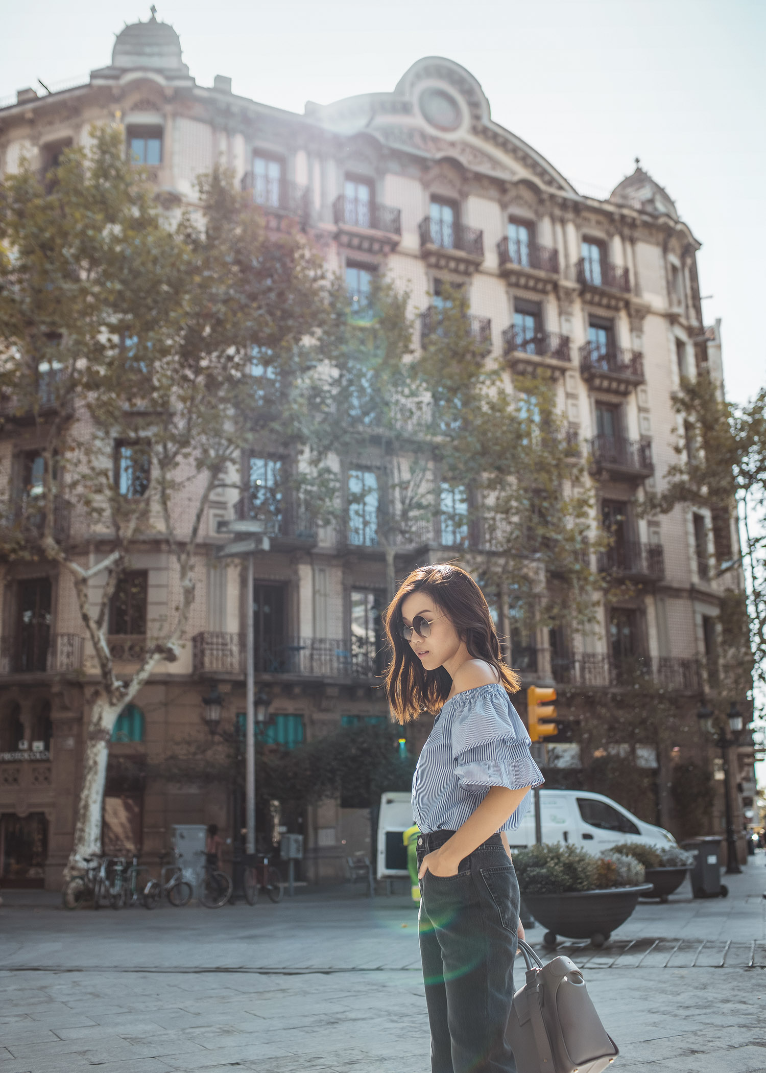 Lifestyle fashion travel blogger Jenny Tsang of Tsangtastic wearing off shoulder ruffle sleeve top and re/done levis jeans and roger vivier leather bag in Barcelona Spain.