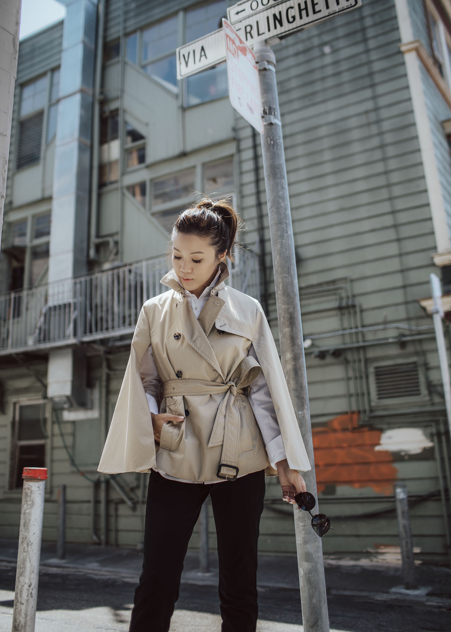 Street style fashion blogger influencer Jenny Tsang of Tsangtastic wearing trench cape white shirt black straight pant sock boots in San Francisco California