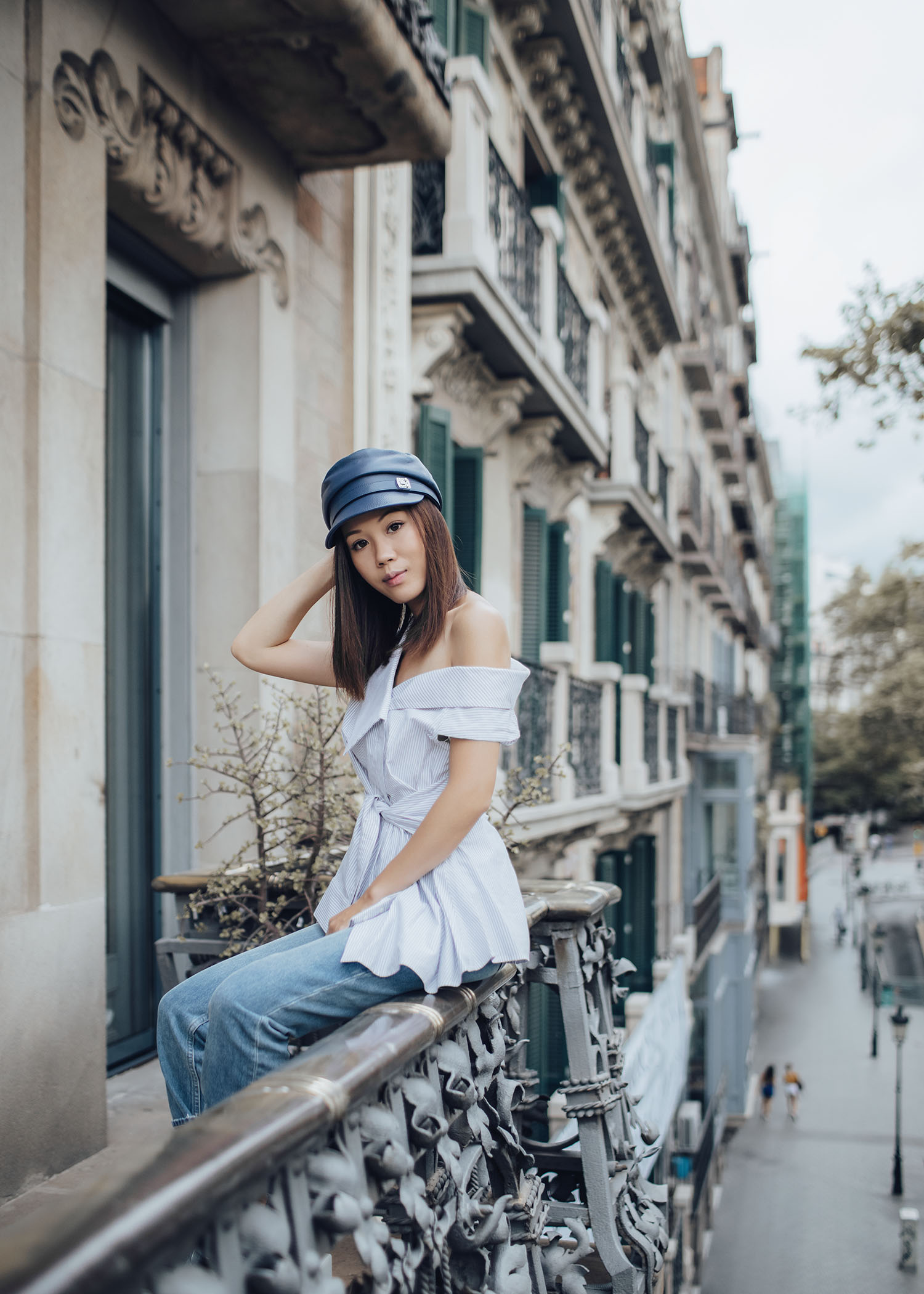 Lifestyle fashion travel blogger Jenny Tsang of Tsangtastic wearing Gucci newsboy leather hat acler off shoulder shirt and Paige sarah jeans in Barcelona Spain