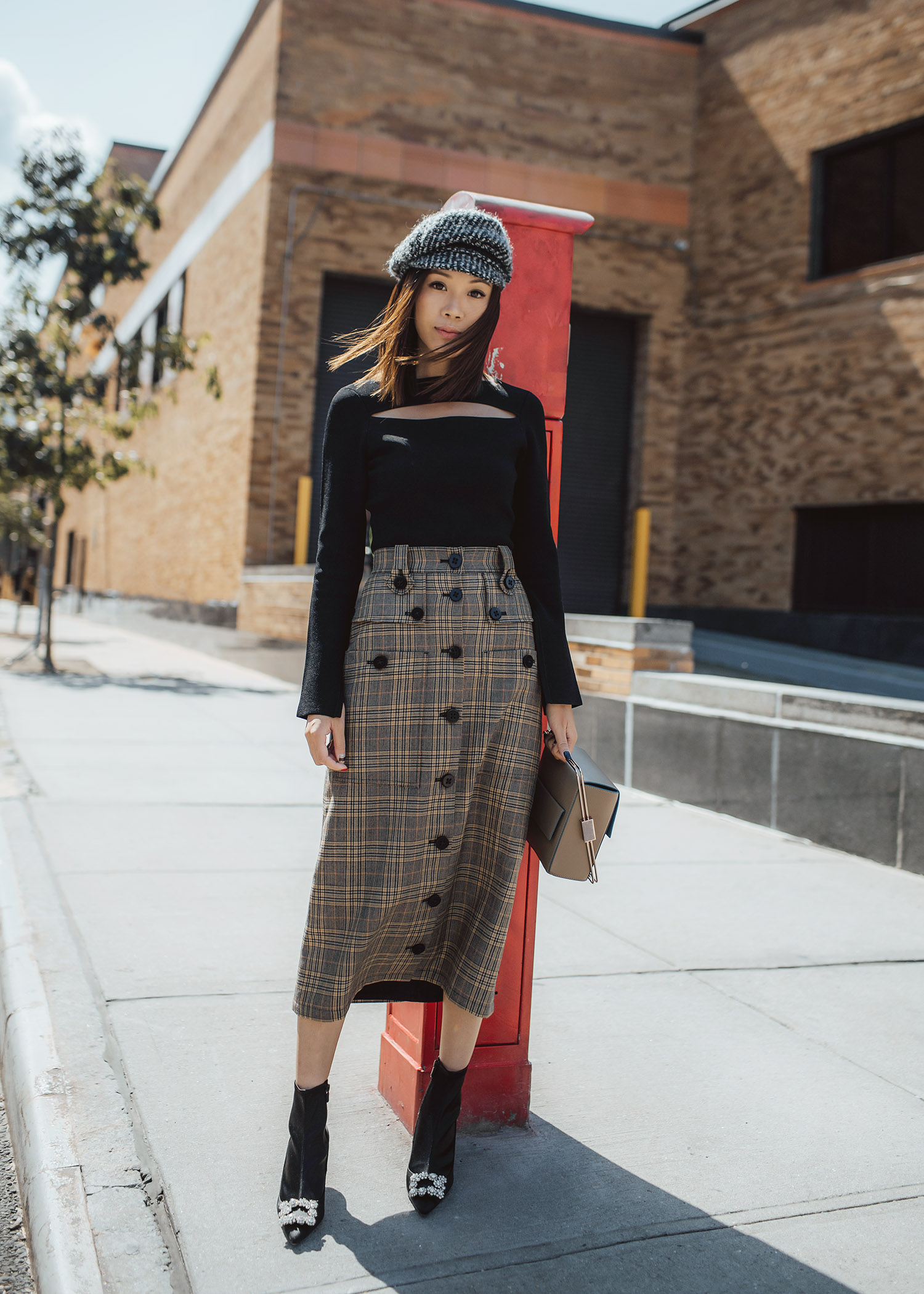 Jenny Tsang of Tsangtastic wearing glen plaid skirt with cream black wool carmella cap hat and roger vivier Jeweled Satin Booties during new york fashion week