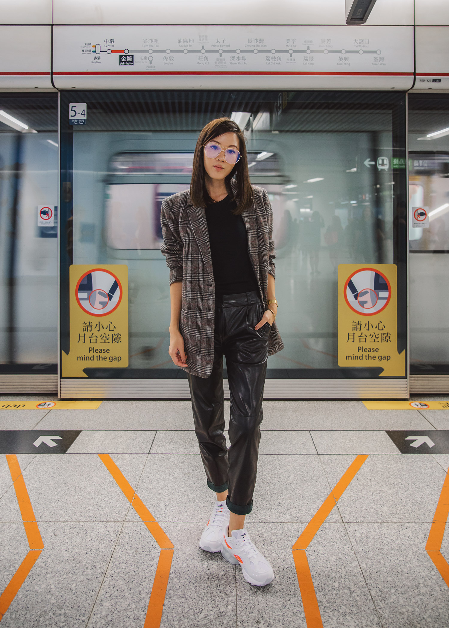 Jenny Tsang of Tsangtastic wearing plaid blazer leather pants daddy sneakers outfit in Hong Kong