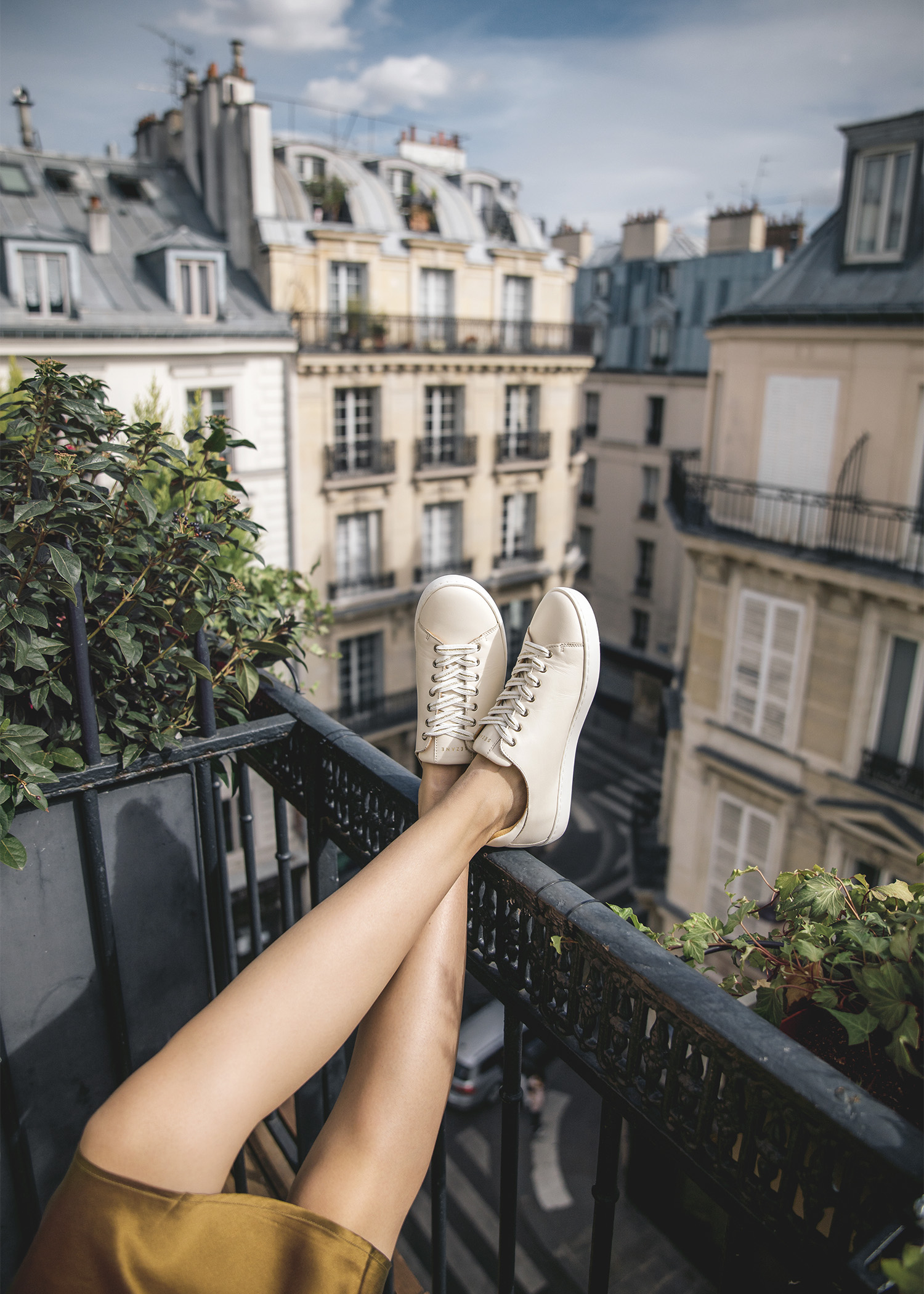 Jenny Tsang of Tsangtastic wearing sneakers and silk dress on balcony in Paris