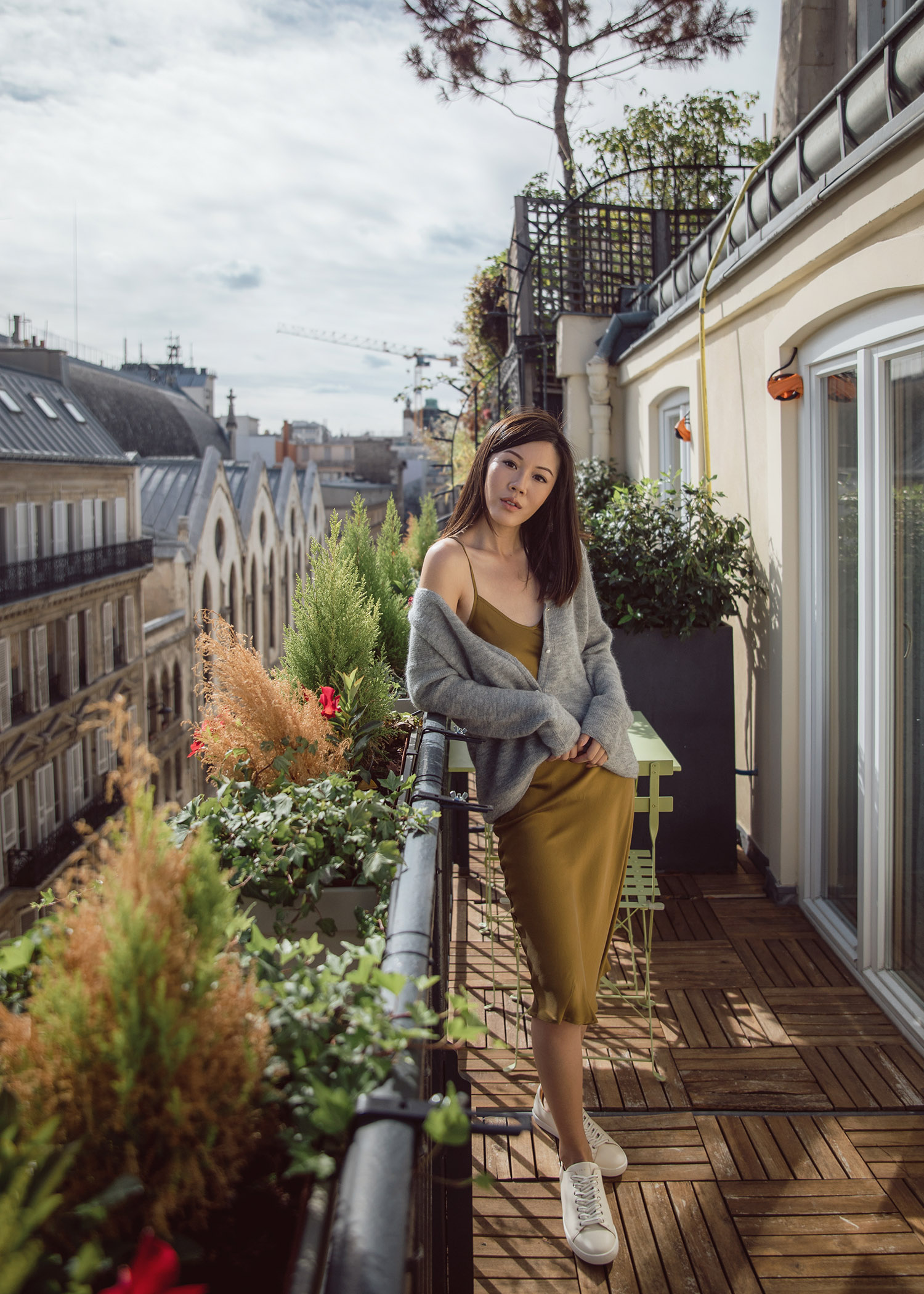 Jenny Tsang of Tsangtastic wearing knit cardigan and silk dress on balcony in Paris