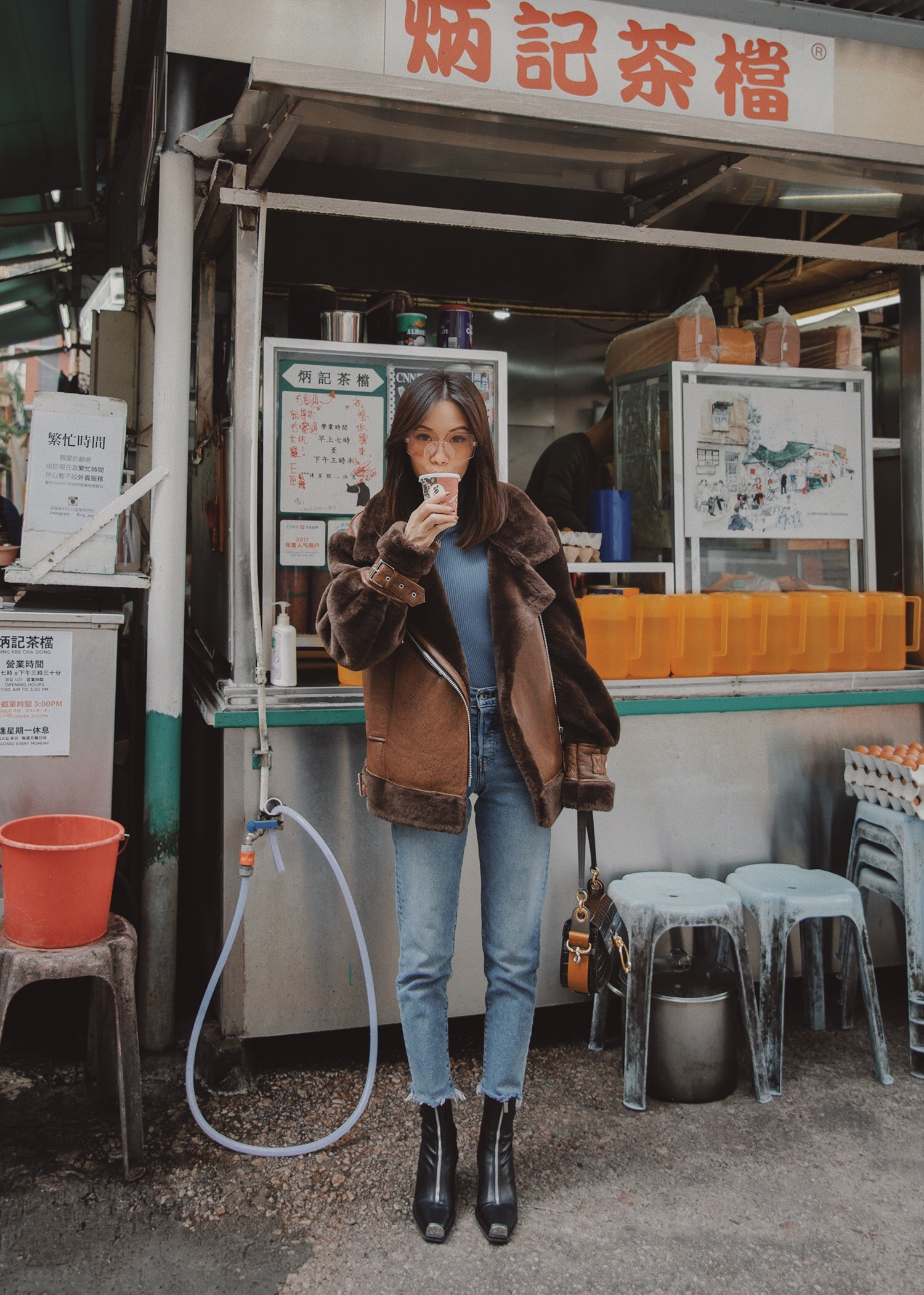 Jenny Tsang of Tsangtastic wearing nicole benisti teddy shearling jacket and levi's wedgie icon jeans in Hong Kong